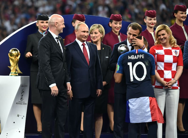 Kylian Mbappe with French President Emmanuel Macron next to FIFA president Gianni Infantino, Russian President Vladimir Putin, Croatian President Kolinda Grabar-Kitarovic and other guests