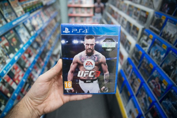 Bratislava, Slovakia, february 12, 2018: Man holding UFC 3 videogame on XBOX One console in store