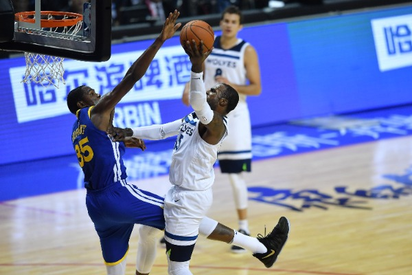 Kevin Durant, left, of Golden State Warriors, attempts to block the shot of Kris Dunn of Minnesota Timberwolves in a basketball match during the NBA China Games in Shanghai, China, 8 October 2017