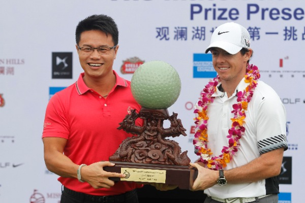 Rory McIlroy of Northern Ireland, right, receives the champion trophy at the award ceremony of The Match at Mission Hills in Haikou city, south Chinas Hainan province, 28 October 2013