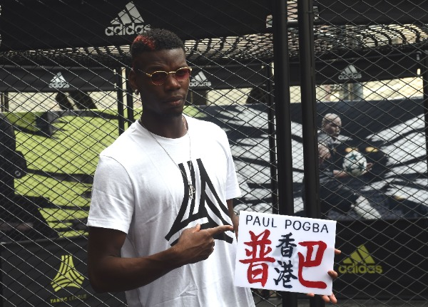 French football player Paul Pogba of English Premier League soccer club Manchester United shows a custom-made Hong Kong minibus emblem reading 'Pogba and Hong Kong' in Chinese, during a promotional event for Adidas Tango League in Hong Kong, China, 1