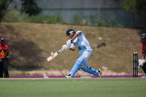 Batsman hitting cricket ball